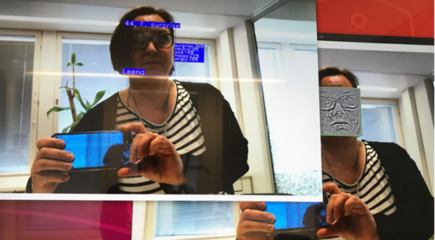 """A woman taking a selfie. The photo on top has the results of the emotion recognition algorithm: """"44, F, surprised"""" overlaid. The bottom screen shows the XAI layer."""